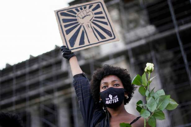 A woman wears a protective face mask on which is written 'Black Lives Matter', and holds a white rose and a placard depicting a fist, during an anti-racism protest. When a Whataburger employee wore her Black Lives Matter mask to work at a Fort Worth Whataburger, a white customer complained about the mask and threatened to call Whataburger's corporate office over the mask. The employee was then told by Whataburger supervisors that her Black Lives Matter mask was inappropriate for work.