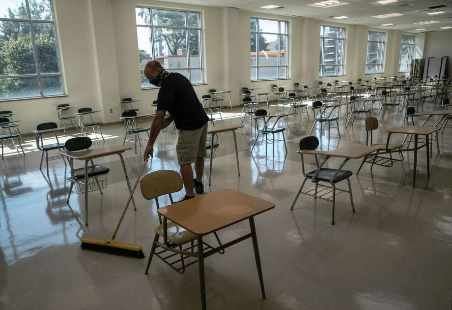 A custodian cleans the school cafeteria between groups of students at lunchtime on the first day of school at Stamford High School on Sept. 8, 2020 in Stamford, Connecticut. Photo: John Moore / Getty Images / 2020 Getty Images