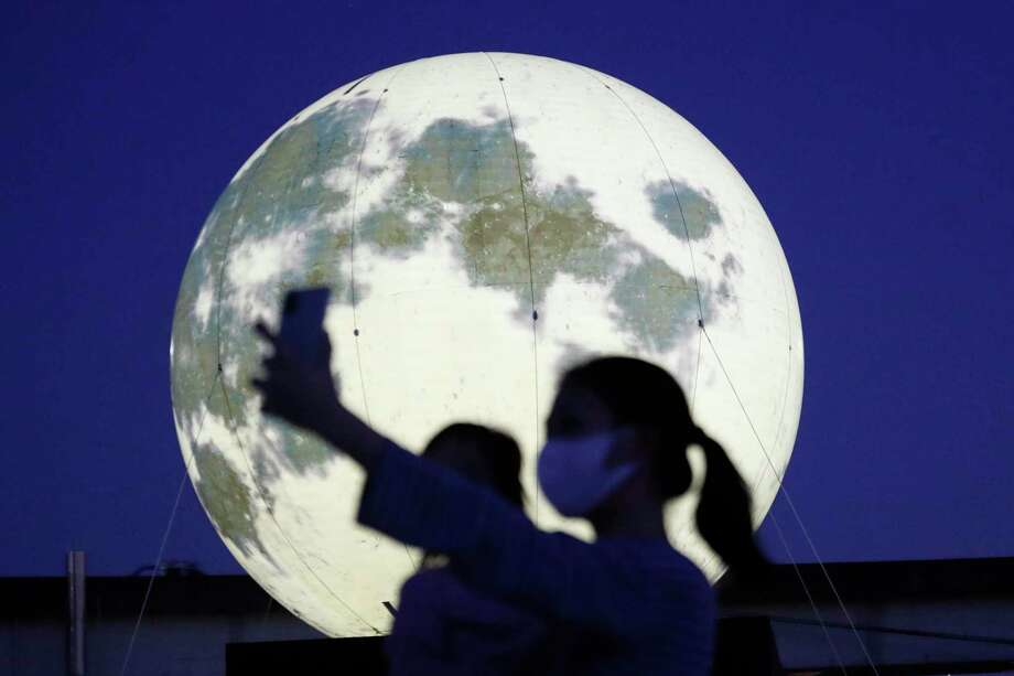 A woman takes a selfie with a glowing full moon installation at a park in Seoul, South Korea, Sept. 18. The artificial full moons were installed by local officials to increase morale during the COVID-19 outbreak and to celebrate the upcoming Chuseok holiday, the Korean version of Thanksgiving Day. In October we'll have the chance to see two real full moons, one of Oct. 1, the other on Halloween. Photo: Ahn Young-joon / Associated Press / Copyright 2020 The Associated Press. All rights reserved.