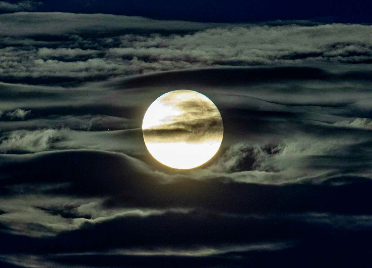The most recent full moon shines through clouds seen from the outskirts of Frankfurt, Germany, early Sept. 2. The next full moon will be on Oct. 1.