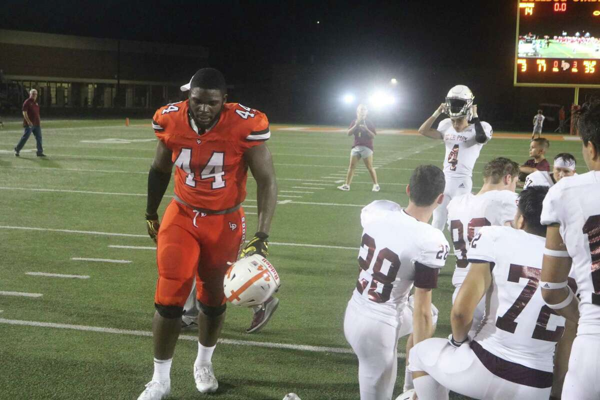 La Porte's Albert Regis walks past the Deer Park postgame huddle, following last year's win by the Bulldogs. Regis is one of the Bulldogs that the Deer coaching staff knows could be trouble tonight.