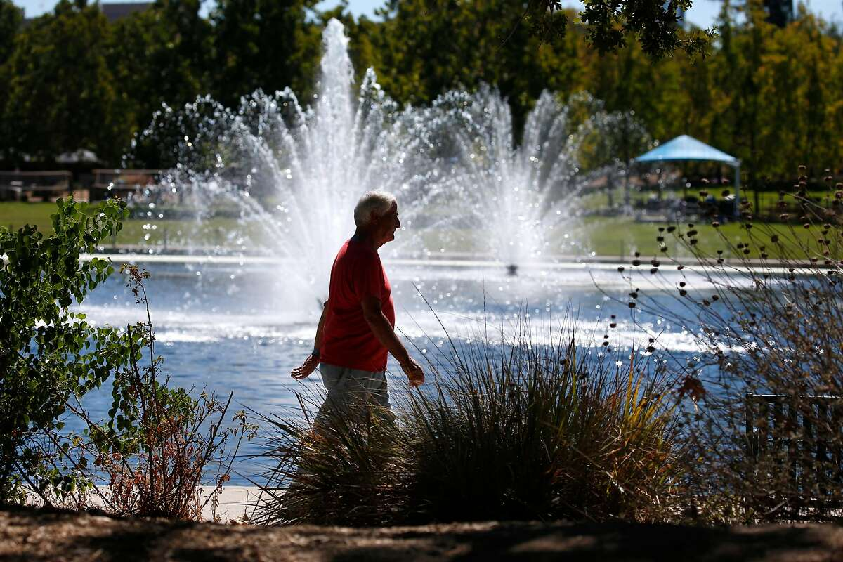 A man walks around the lake at Heather Farm Park in Walnut Creek, Calif. on Thursday, Sept. 24, 2020. Another heat wave is expected to sizzle the Bay Area this weekend. Powerful winds are also expected to gust at higher elevations, prompting a fire weather watch and possible power shut-offs.