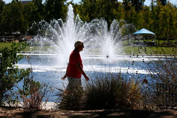 A man walks around the lake at Heather Farm Park in Walnut Creek, Calif. on Thursday, Sept. 24, 2020. Another heat wave is expected to sizzle the Bay Area this weekend.