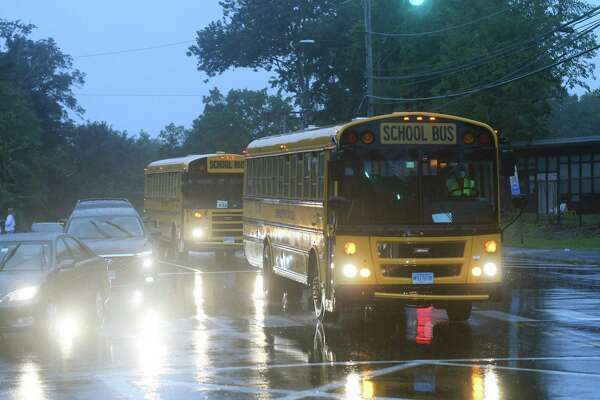 Buses pass by on the first day of the 2020-2021 school year.
