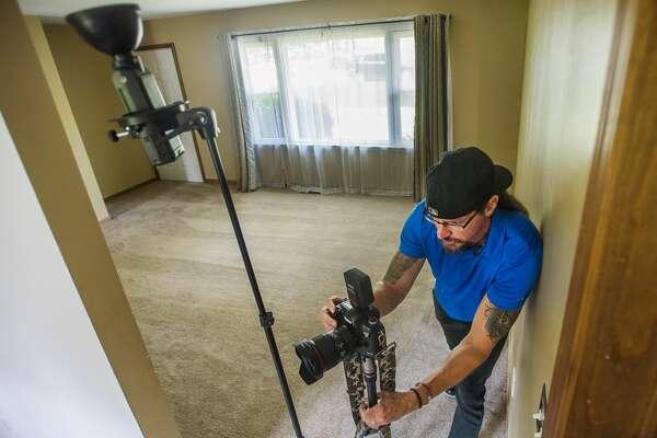 Real estate and freelance photographer Doug Julian photographs a home for sale at 1017 W. Marsh Road near Sanford Lake Wednesday in Sanford. (Katy Kildee/kkildee@mdn.net)