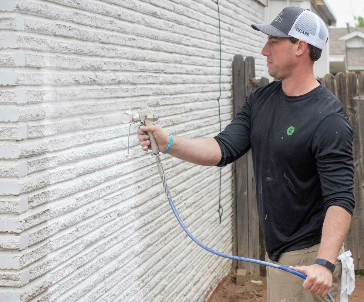Omar Muniz and Mark Walker work on caulking as they and others with EOG Resources 09/25/2020 work on a home in the 3700 block of Cedar Springs Dr. as part of volunteering work with Christmas in Action. Tim Fischer/Reporter-Telegram