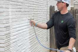 Chris Caskey uses a spray gun to paint the brick 04/16/2021 on a home in the 4500 block of Leddy as part of EOG Resources Christmas in Action. Tim Fischer/Reporter-Telegram