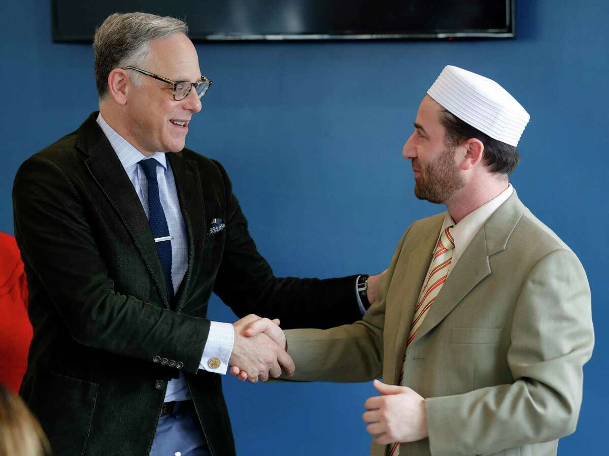 Rabbi Edwin Goldberg, with Congregation Beth Shalom of The Woodlands, left, shakes hands with Imam Rihabi Mohamed, with the Islamic Center of The Woodlands, during Break Bread and Boundaries at Lama Cafe, Wednesday, Jan. 29, 2020, in Shenandoah. Since the COVID-19 pandemic hit the area, the synagogue has been closed but services have been streamed online. For the High Holy Days, Goldberg said Beth Shalom will continue streaming services, and reminds congregants that the mercy they pray for should be given to themselves during these difficult times as well.