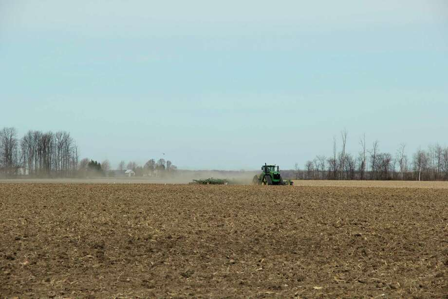 A farm tractor works in the Huron County fields from earlier this year. The USDA announced more funding for farmers who have been affected by the coronavirus pandemic starting this week. (Tribune File Photo)
