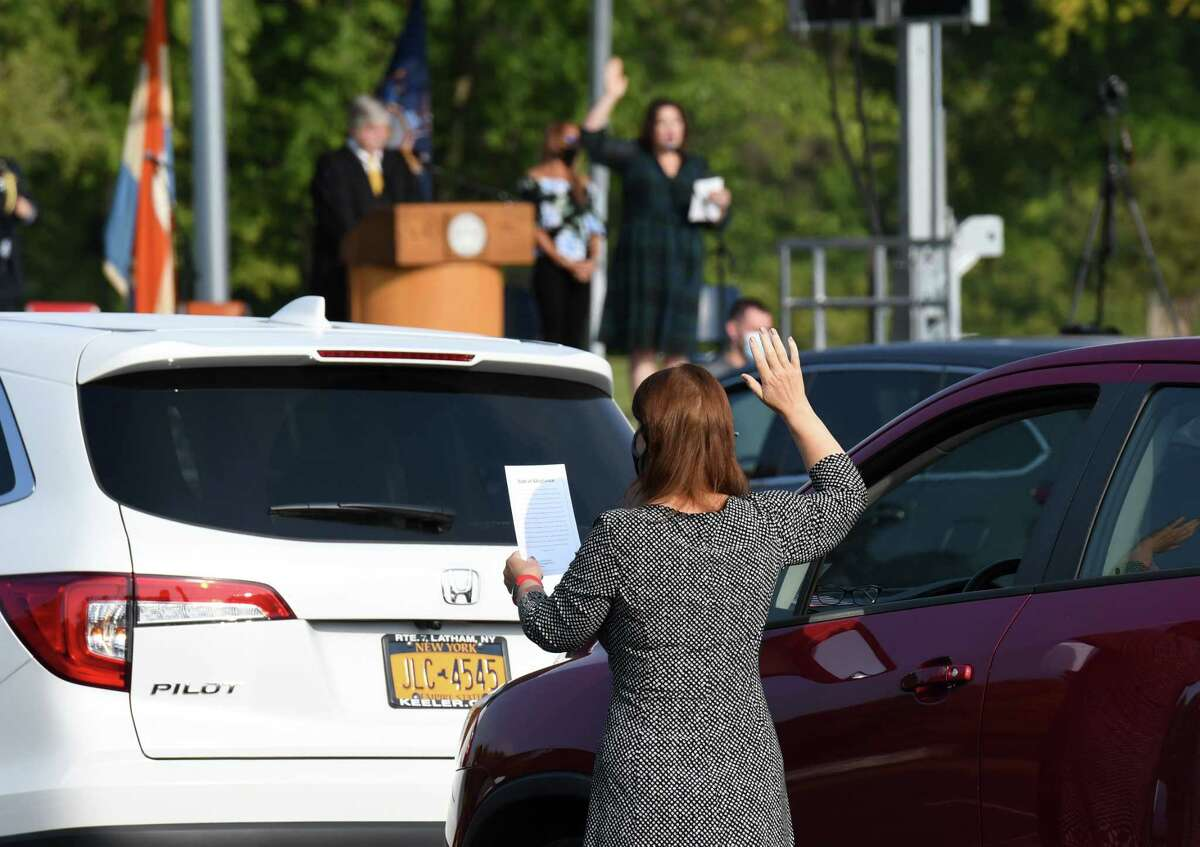 New U.S. citizens raise their right hand and recite the Oath of Allegiance during a drive-in naturalization ceremony on Friday, Sept. 25, 2020, held in the Schenectady County Community College parking lot in Schenectady, N.Y. The ceremony was the first of its kind in New York State. (Will Waldron/Times Union)