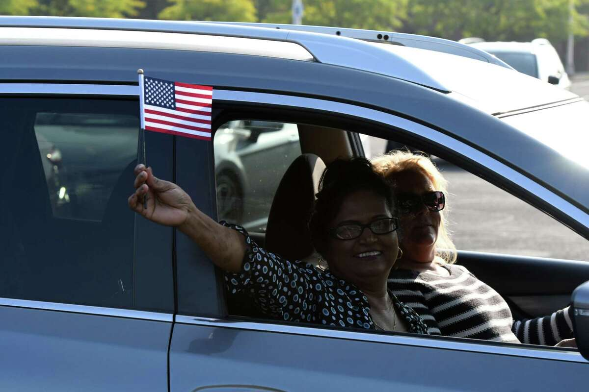 A newly sworn-in U.S. citizen waves her flag following a drive-in naturalization ceremony on Friday, Sept. 25, 2020, held in the Schenectady County Community College parking lot in Schenectady, N.Y. The ceremony was the first of its kind in New York State. (Will Waldron/Times Union)