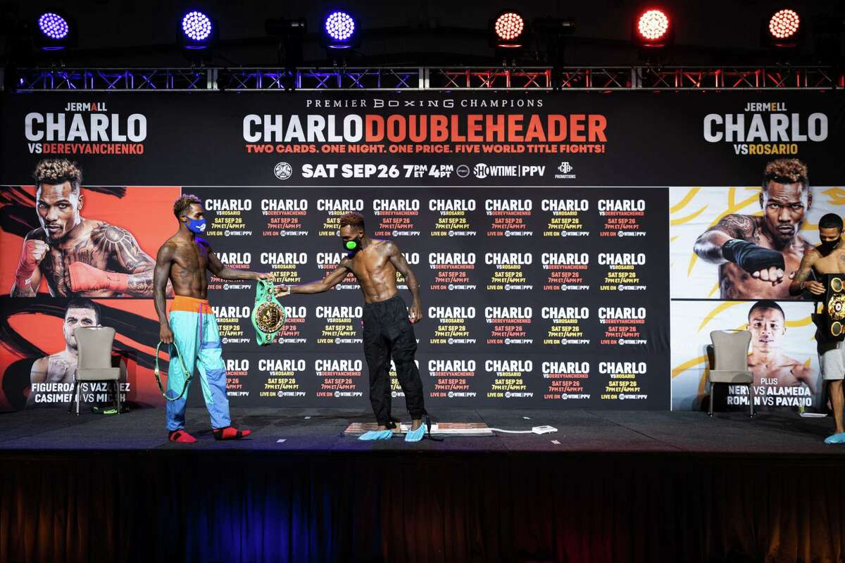 Jermall Charlo (left) hands the WBC super welterweight title to his brother Jermell after the weigh-in Friday, Sept. 25, 2020.
