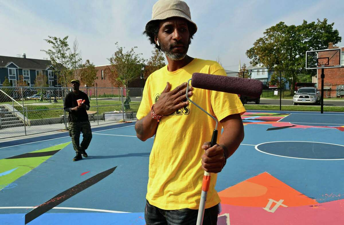 Norwalk Artist Jahmane West works on the mural painted on the surface Ryan Park basketball court Friday, September 25, 2020, in Norwalk, Conn. The mural was part of a roughly $1.1 million effort to rehabilitate the park as part of the federal Choice Neighborhood Initiative grant. The sounds of play were replaced by Jahmane, a South Norwalk native and artist, creating a work of art on his home court.