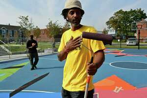 Norwalk Artist Jahmane West works on the mural painted on the surface Ryan Park basketball court Friday, September 25, 2020, in Norwalk, Conn. The mural was part of a roughly $1.1 million effort to rehabilitate the park as part of the federal Choice Neighborhood Initiative grant.