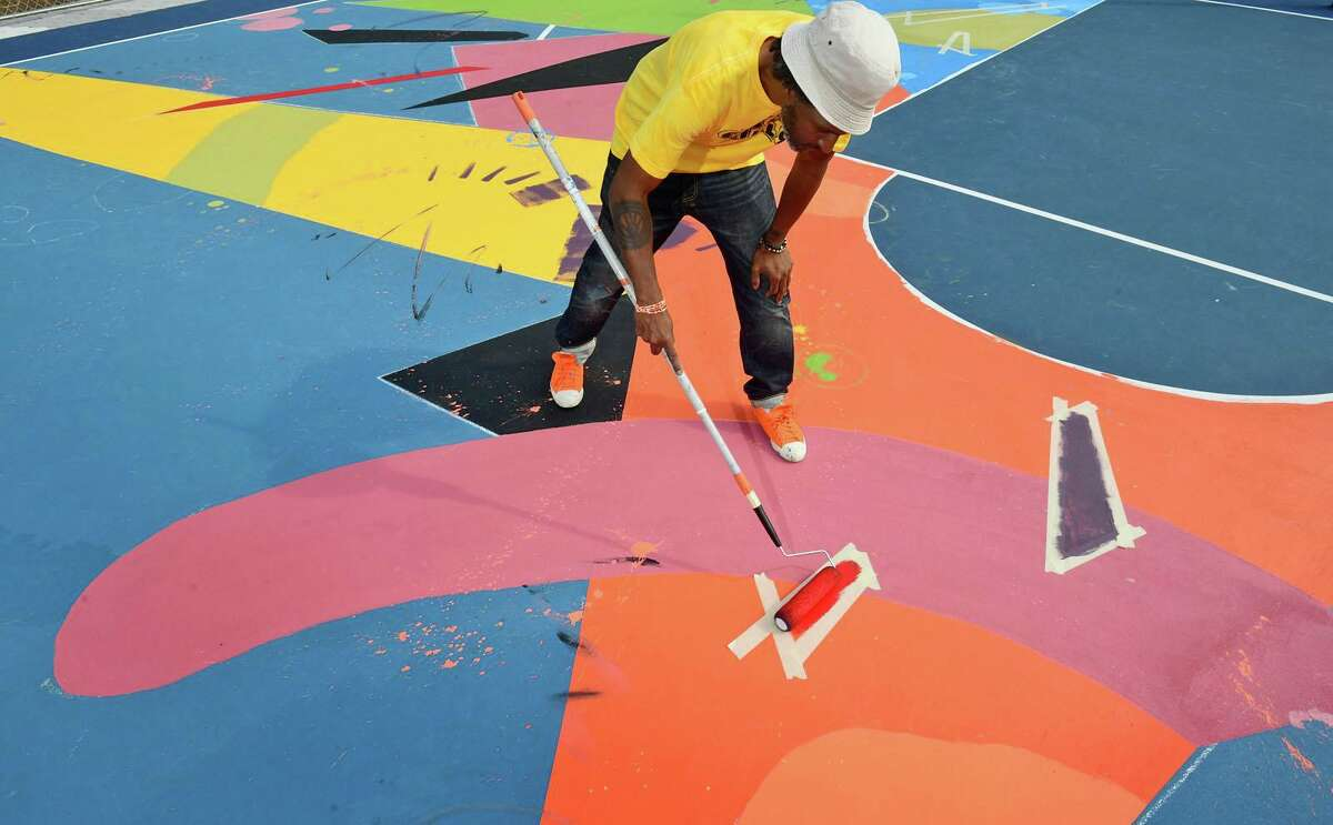 Norwalk Artist Jahmane West works on the mural painted on the surface Ryan Park basketball court Friday, September 25, 2020, in Norwalk, Conn. The mural was part of a roughly $1.1 million effort to rehabilitate the park as part of the federal Choice Neighborhood Initiative grant. Jahmane's work is part of a $1.1 million effort to rehabilitate the park while paying homage to the community's roots. The project is part of the federal Choice Neighborhood Initiative grant which aims to improve housing and intergenerational mobility and build community in distressed neighborhoods. It's the first of five public art pieces being installed in the park.