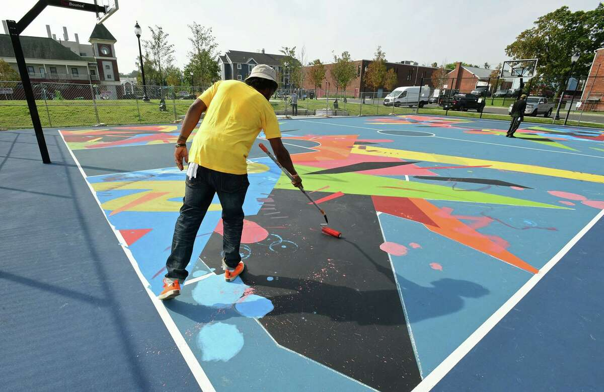 Norwalk Artist Jahmane West works on the mural painted on the surface Ryan Park basketball court Friday, September 25, 2020, in Norwalk, Conn. The mural was part of a roughly $1.1 million effort to rehabilitate the park as part of the federal Choice Neighborhood Initiative grant. Jahmane's work was chosen out of several local artists who submitted proposals for the space. He already has a murual there called