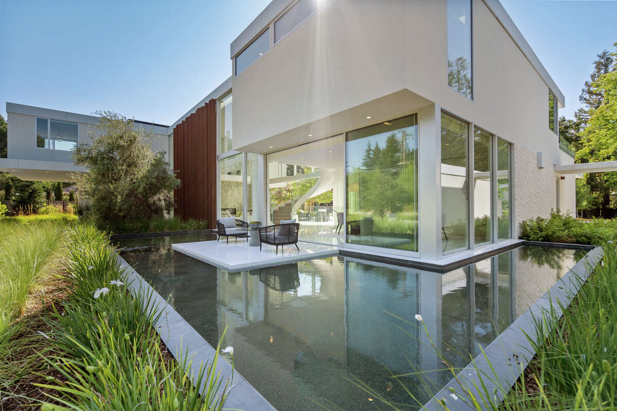 The fantasy starts outside the home, where a wall opens to a patio suspended over water.