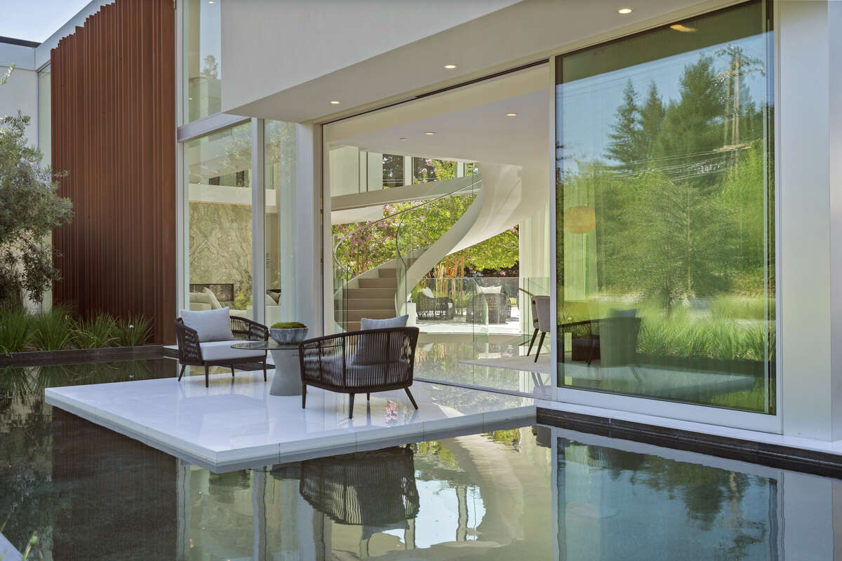 The windows are mostly doors thanks to retracting glass walls throughout the main level. Here we also get a peek of the dramatic swirl of the staircase inside.