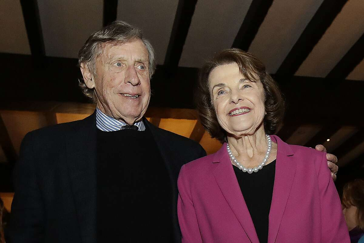 In this Nov. 6, 2018, file photo, U.S. Sen. Dianne Feinstein, right, smiles next to husband Richard Blum at an election night event in San Francisco. Sen. Feinstein's husband, University of California Regent Richard Blum, was named Thursday, Sept. 24, 2020, by the state auditor's office as one of the regents involved in admissions scandal where UC wrongly admitted dozens of wealthy, mostly white students as favors to well-connected people. (AP Photo/Jeff Chiu, File)