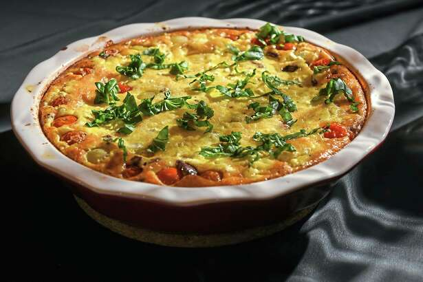 "In her book, ""From the Oven to the Table,"" Diana Henry likens her clafoutis, made with tomato, goat cheese, olives and basil, to a crustless quiche. The soft and light clafoutis does really need accompaniment; it's perfect by itself. (Steve Mellon/TNS)"
