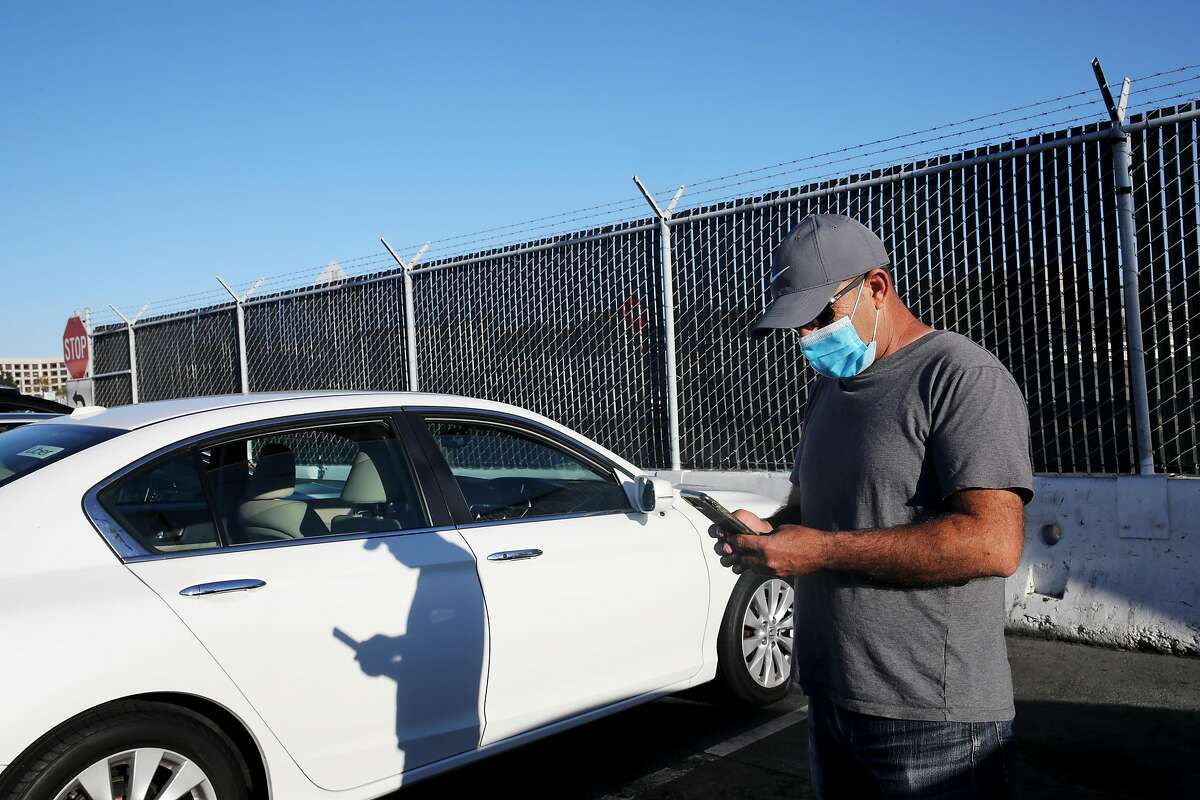 Uber driver Omer Iltas, 43, of San Mateo, looks at his phone from a staging area as he waits to pick up a customer at SFO in August. Drivers as well as riders in California have received messages from ride-hail companies about AB5 and Proposition 22.