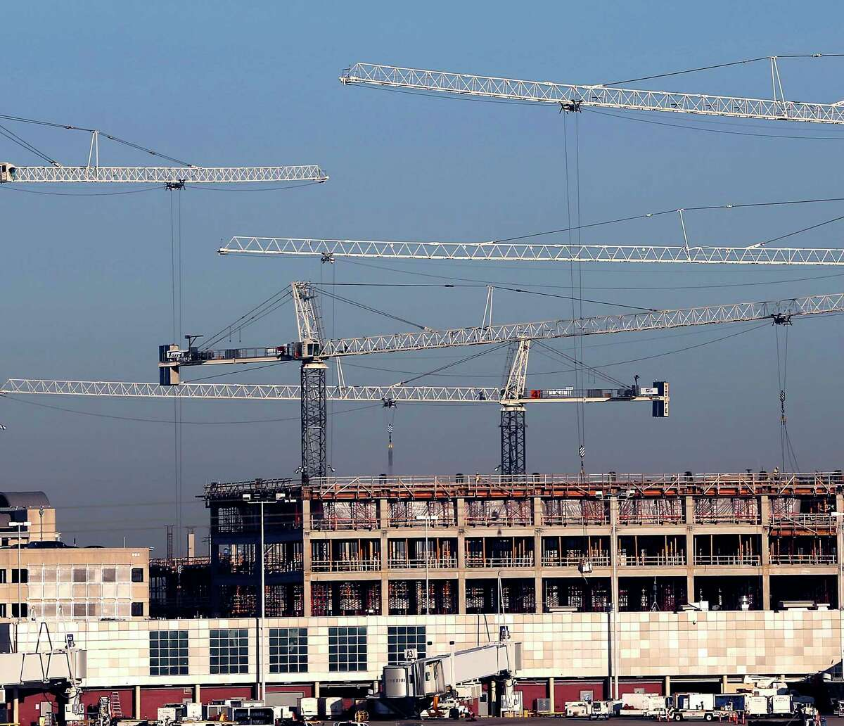 The booms from five tower cranes are seen Wednesday, Dec, 21, 2016 at the San Antonio International Airport as they help construct improvements at the airport, such as a new parking garage seen in the image.