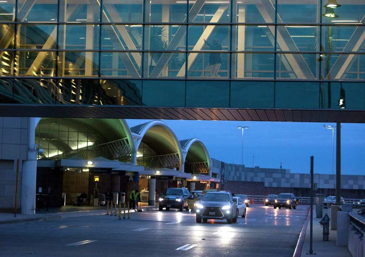 Travelers make their way Wednesday, Nov. 21, 2018 across a pedestrian bridge at San Antonio International Airport the day before Thanksgiving, traditionally one of the busiest travel days of the year.