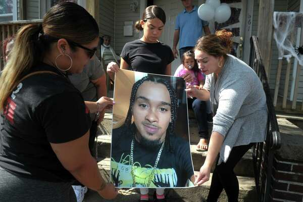 Family members unroll a poster of Raymond Sierra on the front steps of his home in Bridgeport, Conn. Sept. 25, 2020. Sierra, 27, was shot and killed in front of the home Thursday evening.