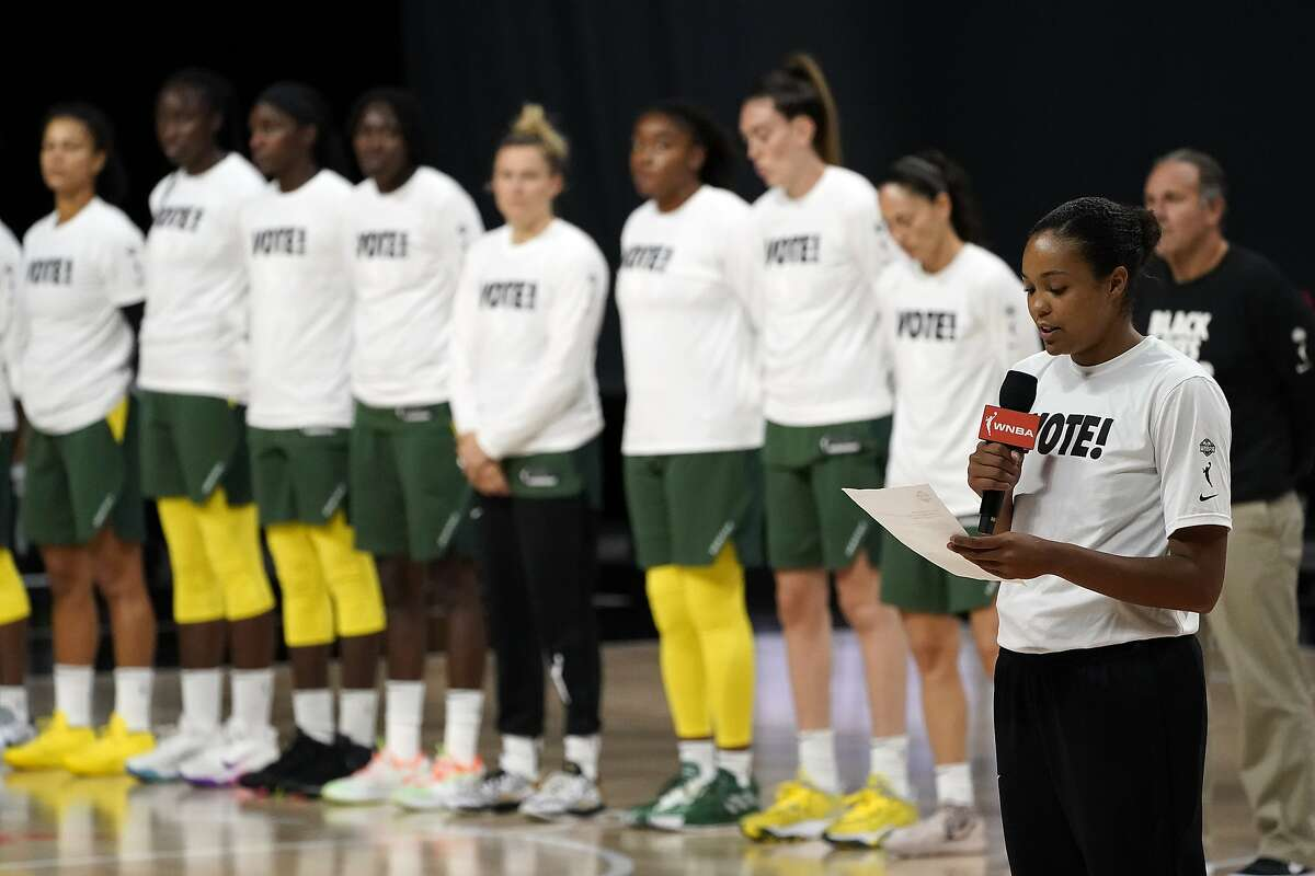 Minnesota Lynx forward Napheesa Collier, right, reads a statement regarding the death of Breonna Taylor before Game 2 of a WNBA basketball semifinal round playoff series Thursday, Sept. 24, 2020, in Bradenton, Fla. Taylor, a 26-year-old woman, was fatally shot by Louisville Metro Police Department in March. Looking on are members of the Seattle Storm. (AP Photo/Chris O'Meara)
