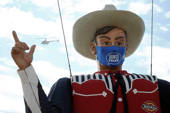 Big Tex, the towering mascot of the State Fair of Texas in Dallas, sports a face mask at this year's celebration. A reader hopes Texans follow his example.