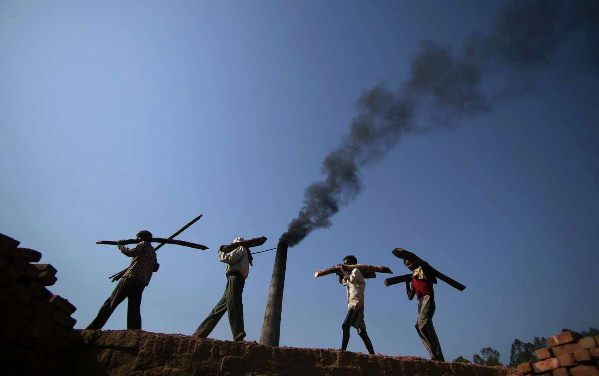 FILE- In this June 4, 2011 file photo, Indian laborers carry firewood, as smoke rises from a bricks factory on the outskirts of Jammu, India.