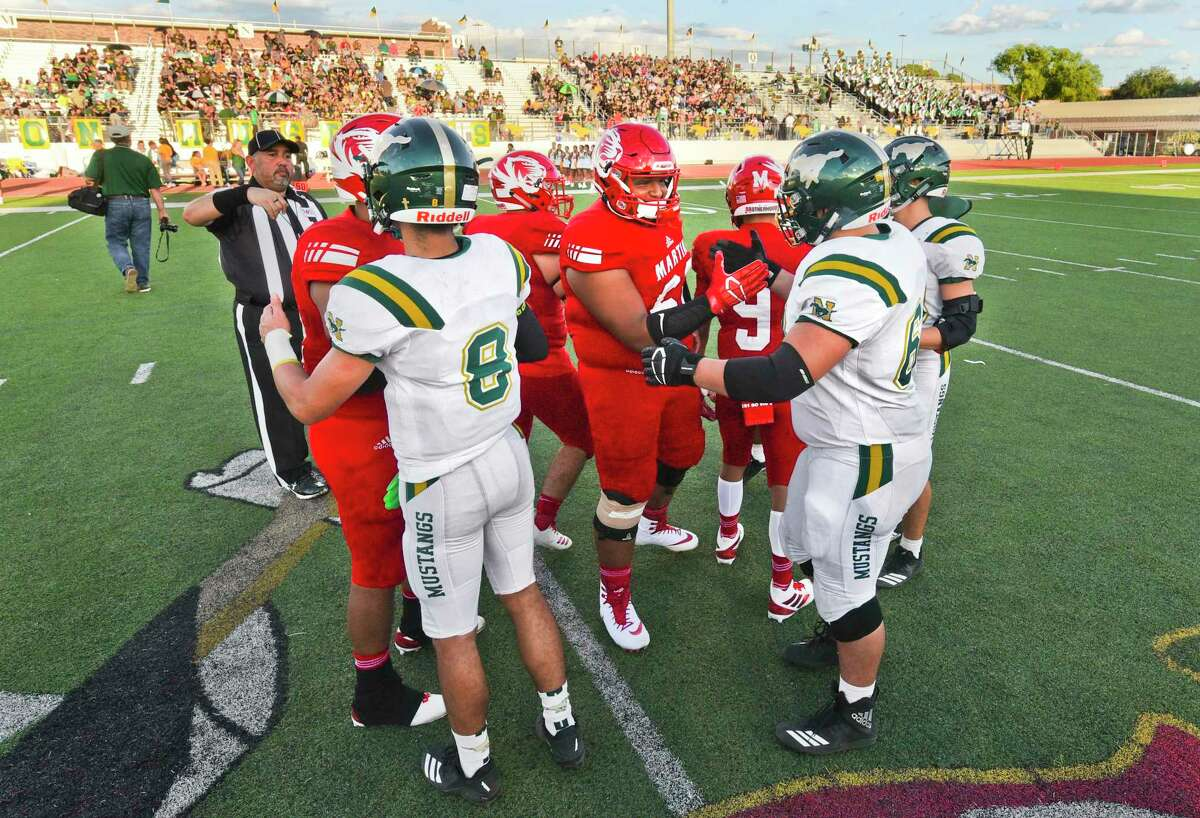 The Nixon High School Mustangs and the Martin High School Tigers greet their opponents, Friday, Aug. 30, 2019, at Shirley Field during the Hammer Bowl rivalry football game.