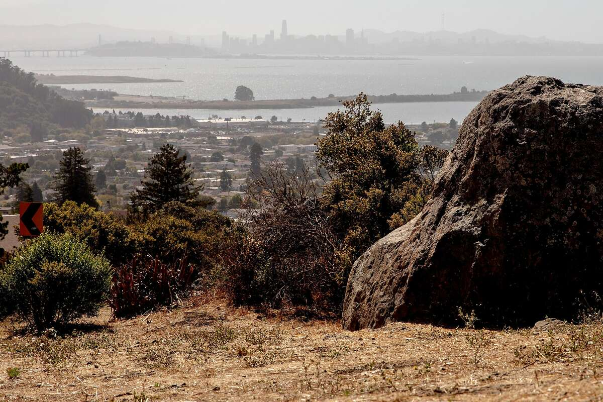 Dry hills sit above homes and businesses seen from Shelvin Drive in El Cerrito, Calif. Friday, September 25, 2020. Heat and strong dry winds have elevated wildfire risks across the Bay Area this weekend, prompting PG&E to warn that some customers may have their power shut off as a result.