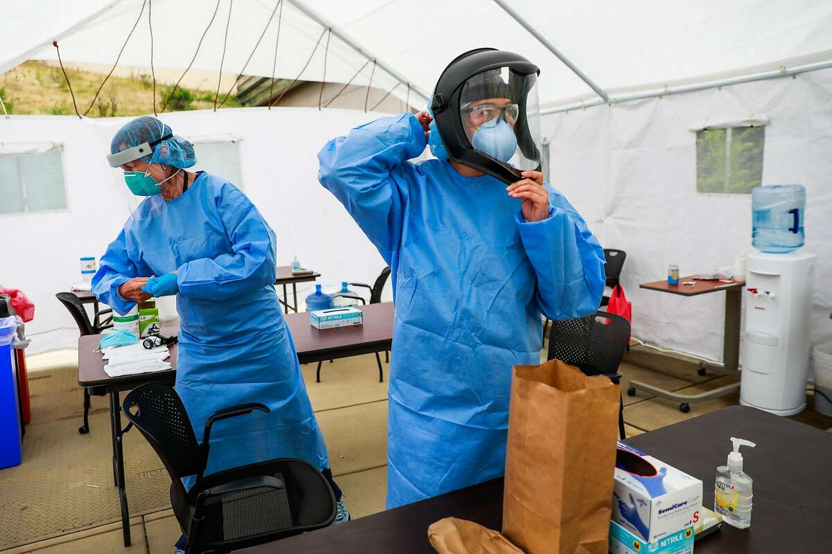 Nurse Rosemary MacLeod (left) and nurse Pauline Tran put on their personal protective equipment before performing Covid-19 tests at Laguna Honda hospital on Thursday, June 25, 2020 in San Francisco, California.