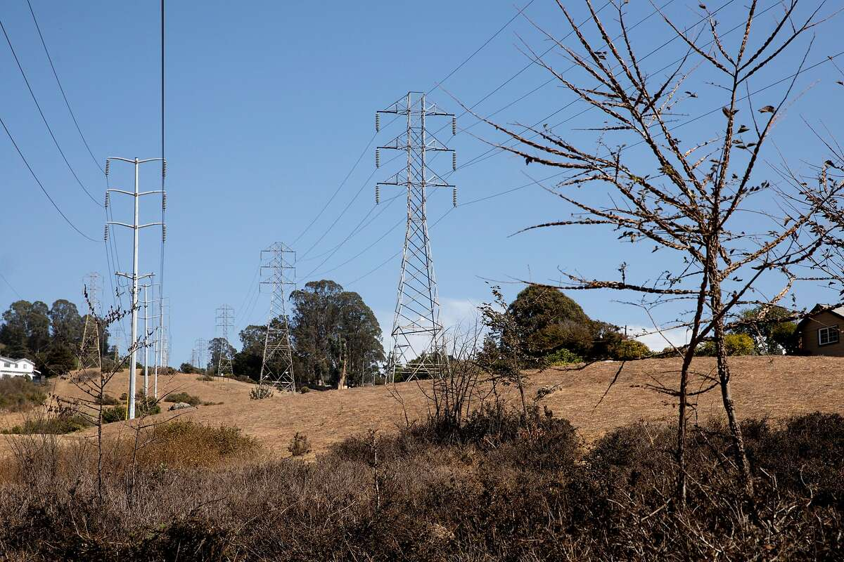 Dry grassy hills and high voltage power lines sit near a row of homes seen from Navellier Street in El Cerrito, Calif. Friday, September 25, 2020. Heat and strong dry winds have elevated wildfire risks across the Bay Area this weekend, prompting PG&E to warn that some customers may have their power shut off as a result.