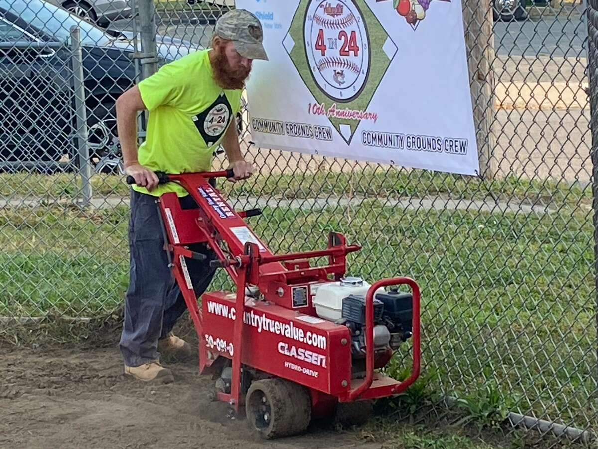 """ValleyCats general manager Matt Callahan works on a Watervliet softball field Friday as part of the """"4 in 24"""" project the team is completing to help area organizations upgrade their facilities.(Mark Singelais / Times Union)"""