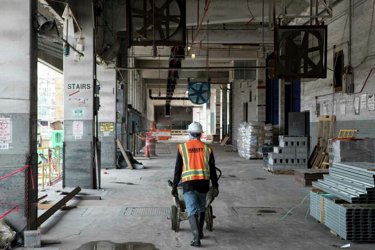 Construction personnel work at POST Houston, the downtown redevelopment of the former Barbara Jordan Post office Thursday, Sept. 24, 2020 in Houston. The historic former Barbara Jordan Post Office is being redeveloped to include a six-acre rooftop farm and park with panoramic skyline views of Houston. Lovett Commercial is developing the space, calling it POST Houston with plans to include experimental shopping options, an international food hall, co-working offices, and a music venue.