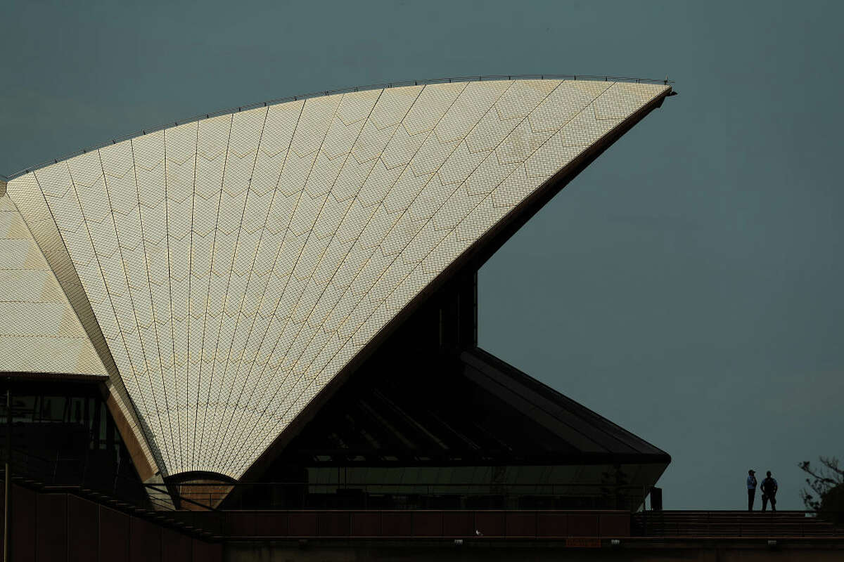 Two policeman stand on the steps of Sydney Opera House in Sydney, Australia, where strict quarantine laws and limits on international arrivals remain in place to ward off COVID-19 outbreaks.