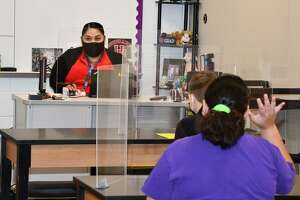 Desk shields protect a teacher and students in a classroom at Watkins Middle School. Cy-Fair ISDhas purchased 13,600 desk shields for teachers and 102,000 shields for students.