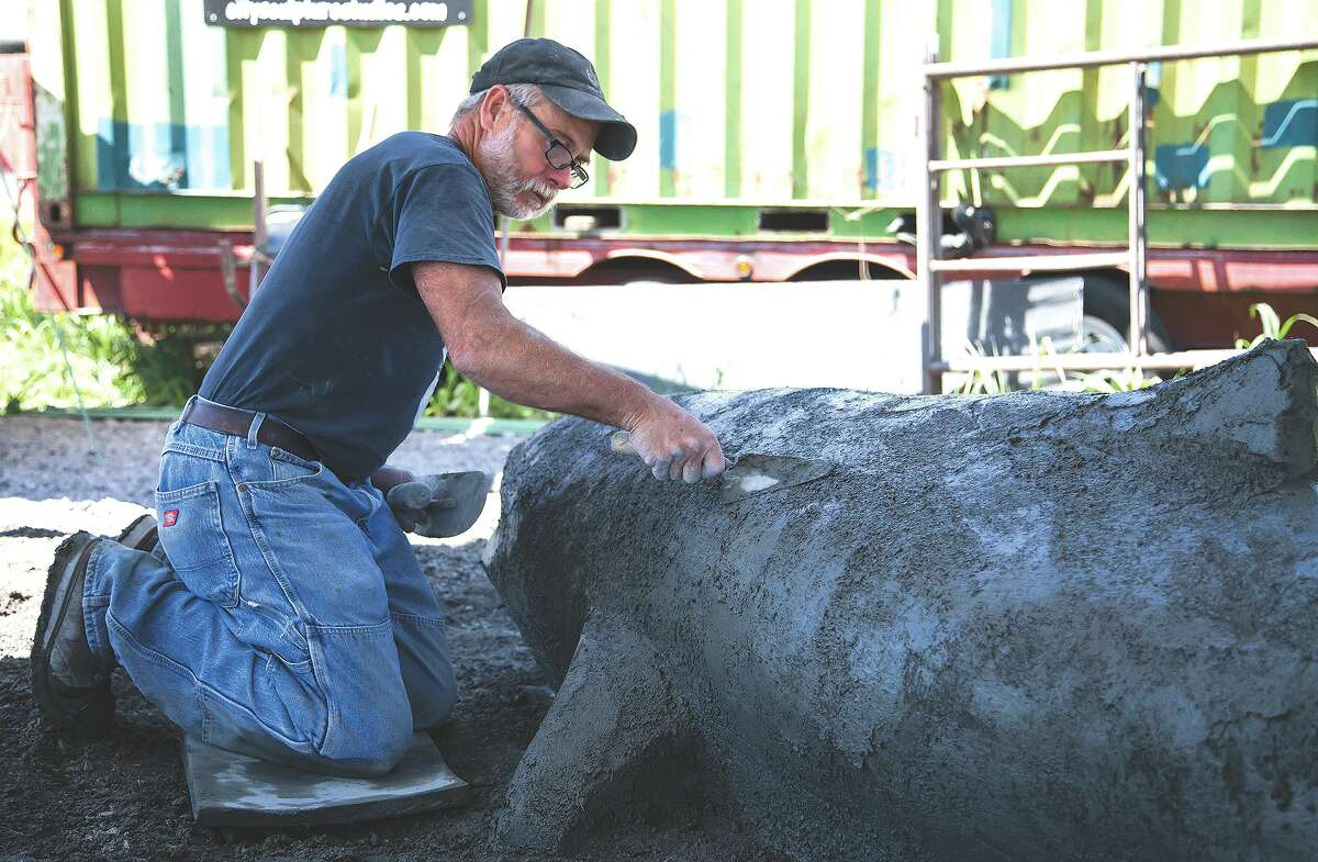 Concrete sculptor Kurt Knickmeyer molds and smooths the concrete form of one of the catfish sculptures to grace the riverfront in Grafton during work in August. Knickmeyer and two other sculptors created a large turtle and frog sculpture, in addition to two catfish sculptures.