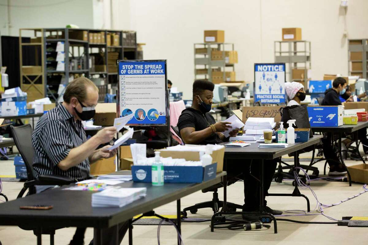 Harris County workers prepare early voting mail-in ballot envelopes to be sent to voters from the Harris County Clerk's election headquarters at the NRG Arena on Friday, Sept. 25, 2020, in Houston.