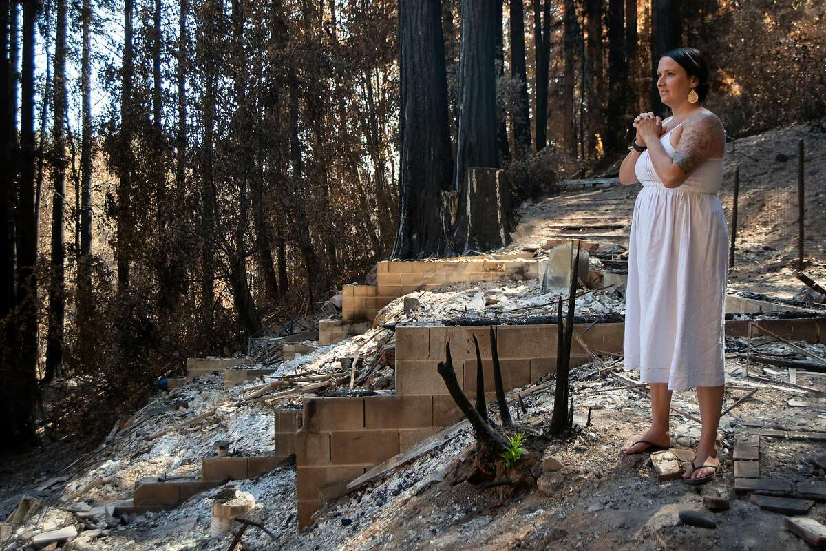 Antonia Bradford stands next to what's left of her home in Boulder Creek after it was decimated by the CZU Lightning Complex Fire, Sept. 23, 2020. New growth starting to peak through the charred remains of foliage gives her some hope looking forward.