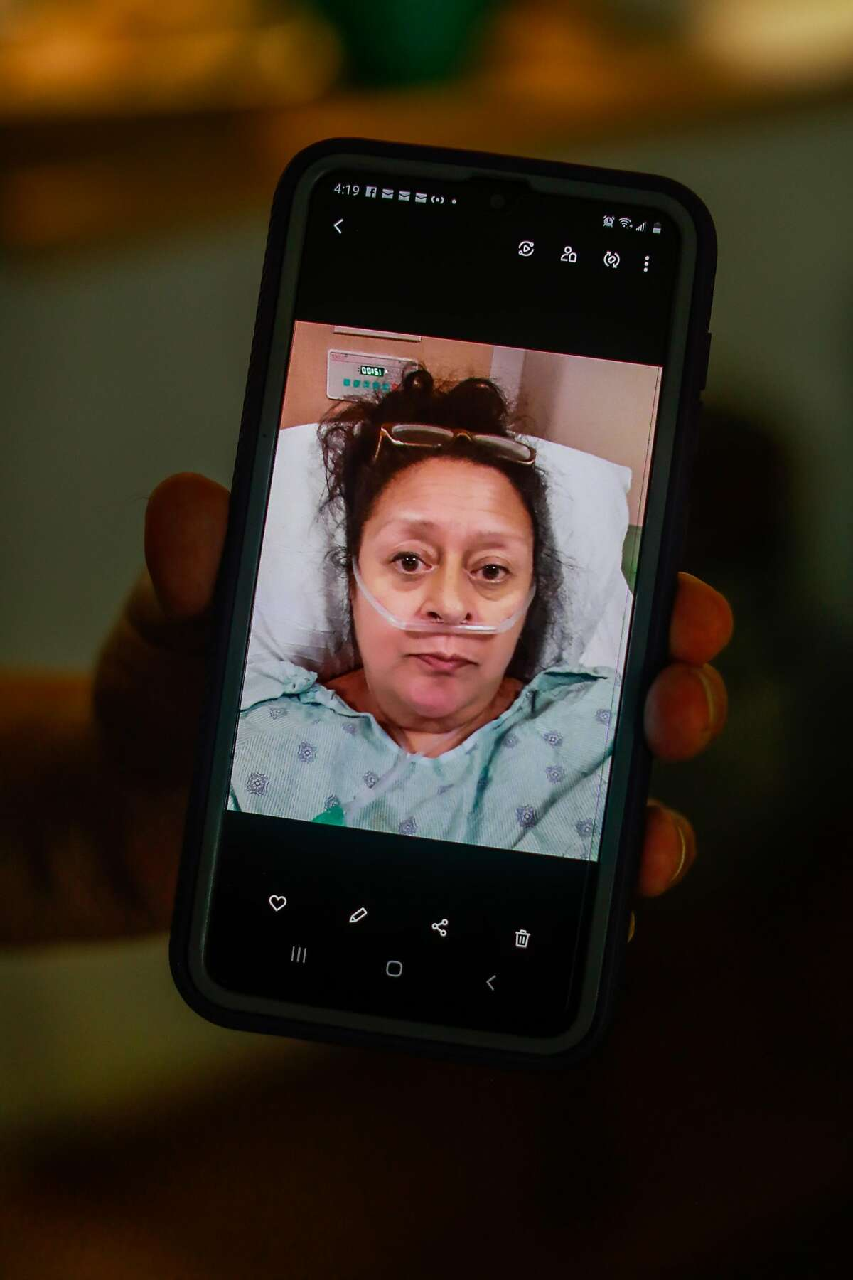 Charlotte Juarez shows a photo from her phone from when she was in the hospital on Thursday, Sept. 24, 2020 in Burlingame, California. Charlotte was in the hospital with the coronavirus in June and is still experiencing lingering effects including fatigue and heart palpitations.