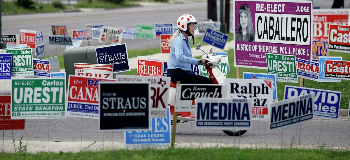 A woman on a scooter passes a sea of election signs at an early voting polling site, Wednesday, May 23, 2012, in San Antonio. Election day in Texas is May 29th. (AP Photo/Eric Gay)