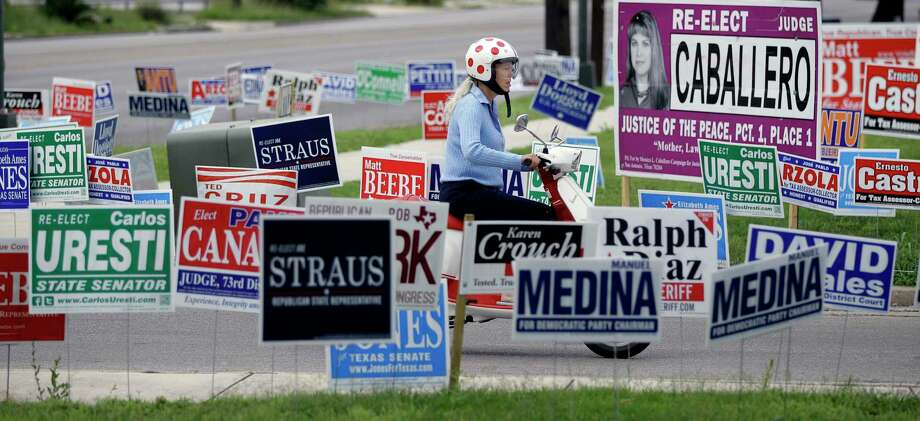 A woman on a scooter passes a sea of election signs at an early voting polling site, Wednesday, May 23, 2012, in San Antonio. Election day in Texas is May 29th. (AP Photo/Eric Gay) Photo: Eric Gay, STF / AP / AP