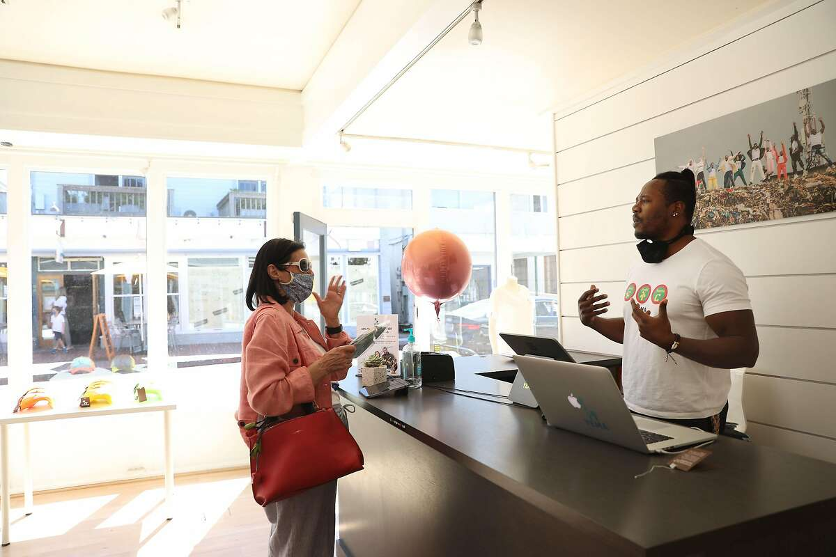 Yema Khalif (right),co-founder Yema, talks with customer Anna Edwards (left), of Concord, as she makes a purchase at Yema on Wednesday, September 23, 2020 in Tiburon, Calif.