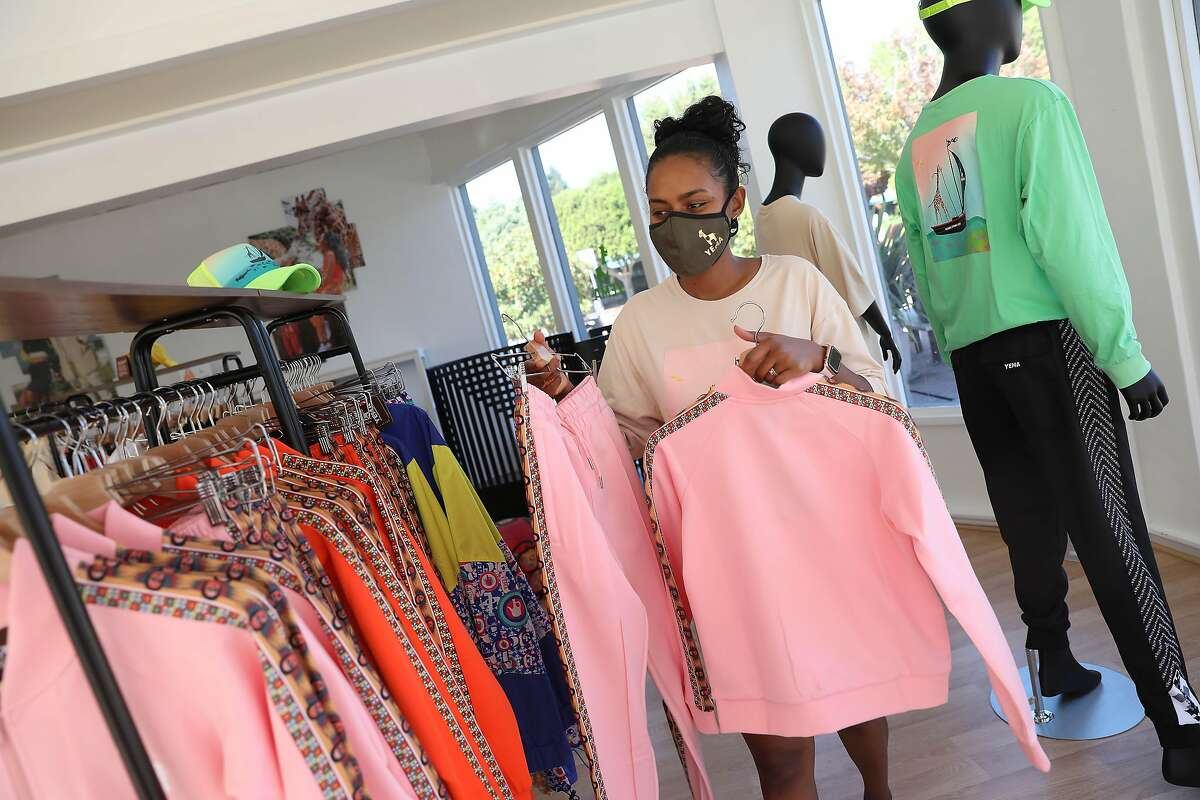 Hawi Awash, Yema co-founder, hangs Yema clothing for sale on racks while working at Yema on Wednesday, September 23, 2020 in Tiburon, Calif.