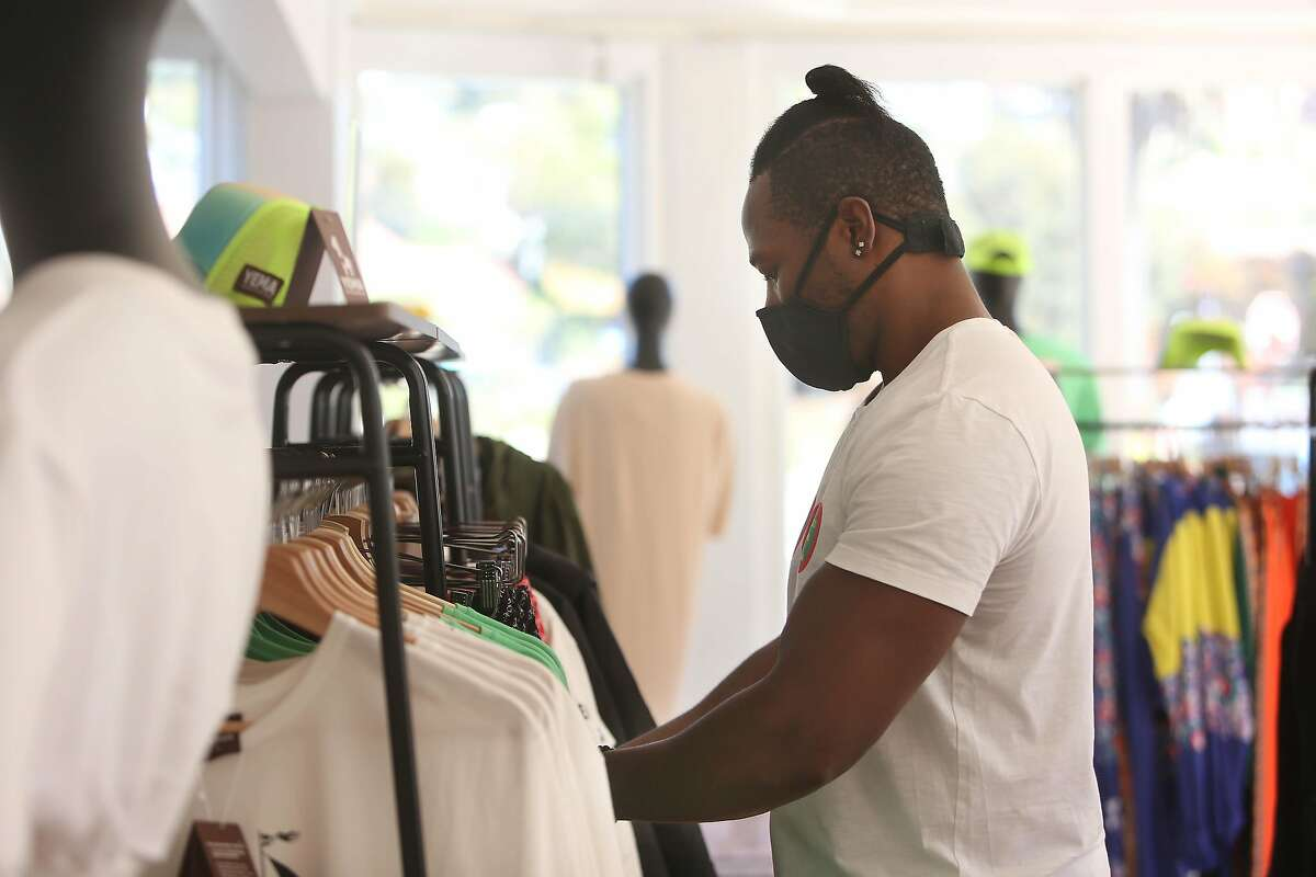 Khalif arranges clothing on a rack. The store owners are suing after an August altercation with police from Tiburon and Belvedere.