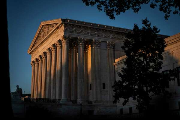 The sun sets as people gather to pay respects to Justice Ruth Bader Ginsburg in front of the Supreme Court Monday.