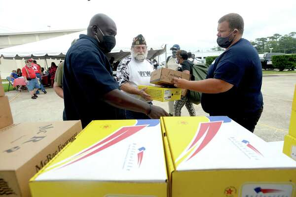Albert Darby (left) and Donald Lotman gather boxes of boots donated from area army bases for veteran Jeff Courts during the annual Southeast Texas Stand Down 2020 held at the Veteran's Center in Beaumont Friday. Multiple services, agencies, and give-aways were available for veterans and the homeless. Similar events are held through the year in other Southeast Texas locations, including one in May in Orange and in January in Port Arthur. Photo taken Friday, September 25, 2020 Kim Brent/The Enterprise
